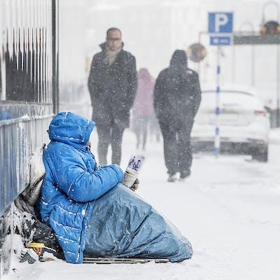 En person i blå jacka som sitter på marken och tigger.