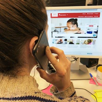 Man håller smartphone i handen framför en datorskärm med 1177 hemsidan Vårdguiden uppe.